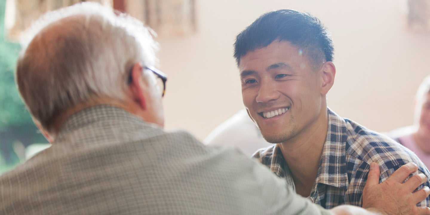 An older man talking to a younger man