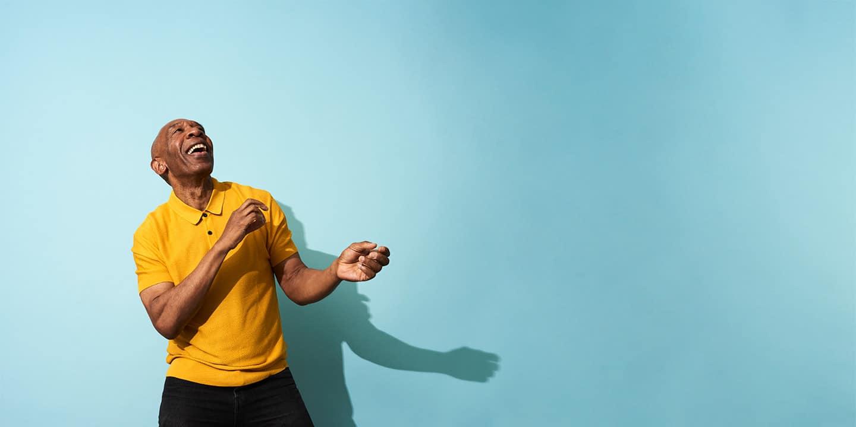 Man in yellow shirt dancing and smiling