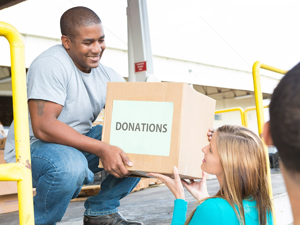 A man and a woman unloading boxes of donations