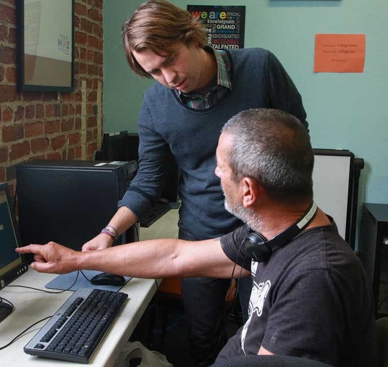 Man offering computer assistance to another