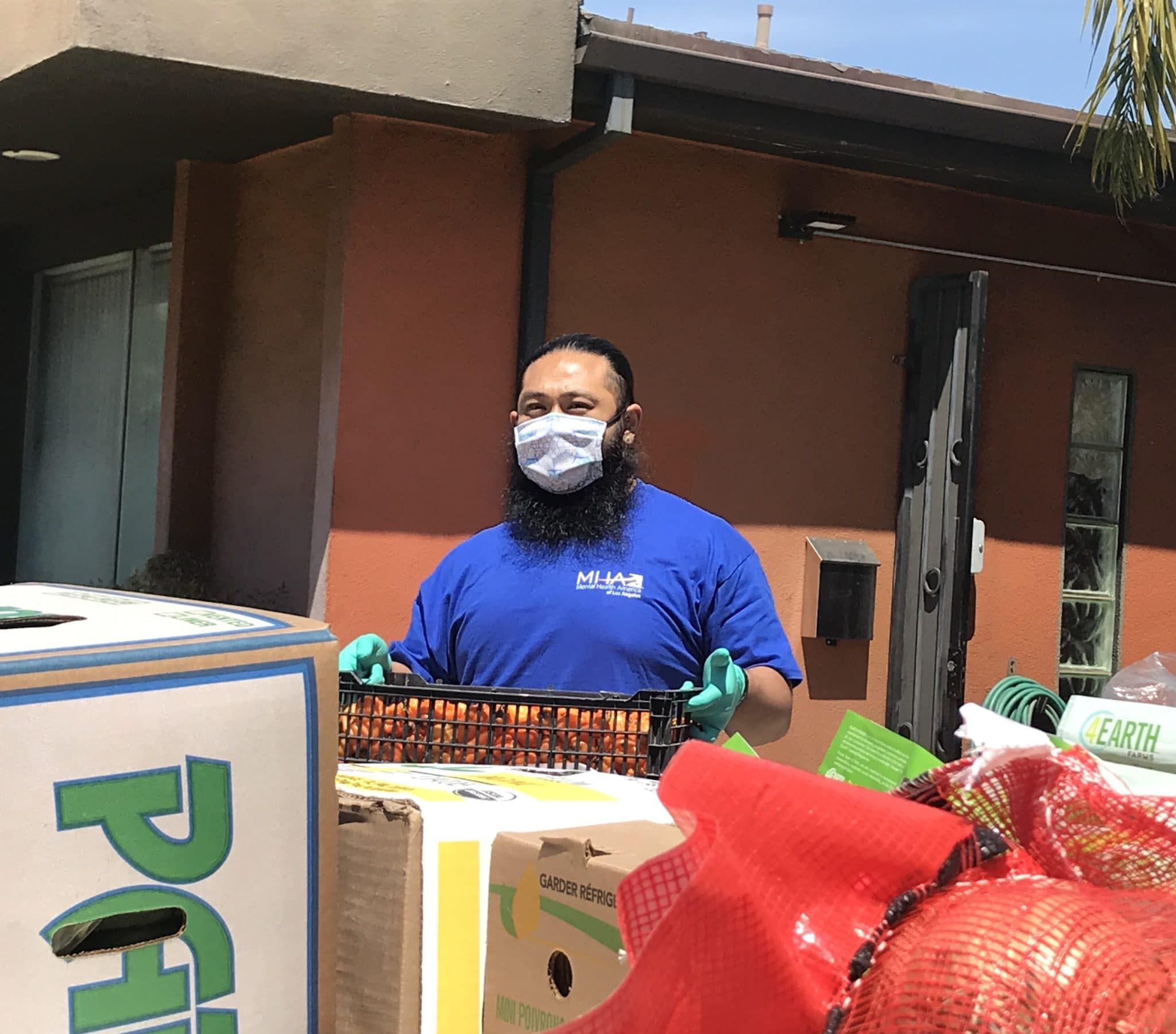 Man wearing mask carrying crate of produce